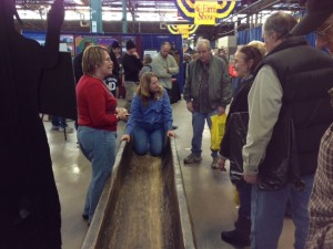 Curator Janet Johnson demonstrates the functionality of the dugout at the Farm Show